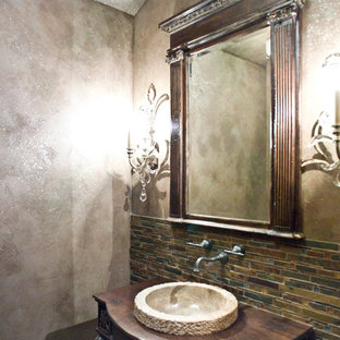 This is an example of a medium sized rustic cloakroom in Other with freestanding cabinets, dark wood cabinets, multi-coloured tiles, mosaic tiles, multi-coloured walls, porcelain flooring, a vessel sink, wooden worktops and grey floors.