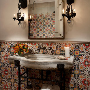 Photo of an expansive mediterranean powder room in Phoenix with flat-panel cabinets, medium wood cabinets, a one-piece toilet, beige tile, mosaic tile, beige walls, porcelain floors, a vessel sink and granite benchtops.