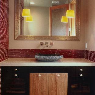 Imagen de aseo de estilo zen, de tamaño medio, con lavabo sobreencimera, armarios con paneles lisos, puertas de armario de madera en tonos medios, sanitario de una pieza, baldosas y/o azulejos rojos, paredes beige, suelo de bambú y azulejos en listel