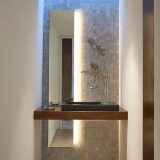 На фото: туалет в современном стиле с бежевой плиткой, каменной плиткой, белыми стенами, настольной раковиной, столешницей из дерева, бетонным полом и коричневой столешницей с