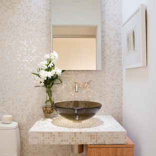 Design ideas for a contemporary cloakroom in Los Angeles with light wood cabinets, a one-piece toilet, beige tiles, mosaic tiles, white walls, a vessel sink, tiled worktops and flat-panel cabinets.