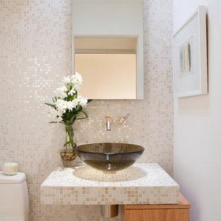 Идея дизайна: туалет в современном стиле с светлыми деревянными фасадами, унитазом-моноблоком, бежевой плиткой, плиткой мозаикой, белыми стенами, настольной раковиной, столешницей из плитки и плоскими фасадами