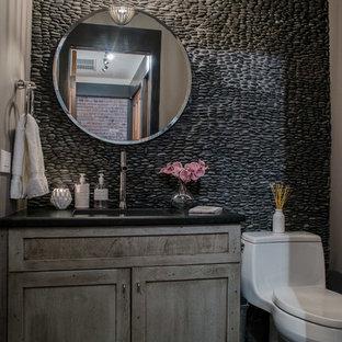 フィラデルフィアの小さいインダストリアルスタイルのおしゃれなトイレ・洗面所 (シェーカースタイル扉のキャビネット、ヴィンテージ仕上げキャビネット、一体型トイレ、石タイル、オーバーカウンターシンク、クオーツストーンの洗面台、グレーの床) の写真