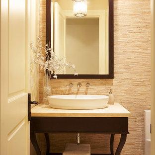 Cette photo montre un WC et toilettes chic de taille moyenne avec un placard sans porte, des portes de placard en bois sombre, un carrelage beige, un carrelage marron, un carrelage de pierre, un sol en travertin, une vasque, un plan de toilette en marbre et un sol marron.