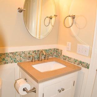 Esempio di un piccolo bagno di servizio american style con lavabo sottopiano, ante bianche, top in superficie solida, WC a due pezzi, piastrelle multicolore, piastrelle di ciottoli, pareti beige, pavimento in gres porcellanato e ante con riquadro incassato