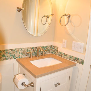 Photo of a small traditional cloakroom in Other with a submerged sink, white cabinets, solid surface worktops, a two-piece toilet, multi-coloured tiles, pebble tiles, beige walls, porcelain flooring and recessed-panel cabinets.