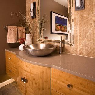 Пример оригинального дизайна интерьера: туалет в стиле фьюжн с настольной раковиной, плоскими фасадами, фасадами цвета дерева среднего тона, бежевой плиткой, мраморной плиткой и коричневой столешницей