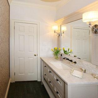 Foto på ett stort vintage vit toalett, med möbel-liknande, vita skåp, en toalettstol med separat cisternkåpa, beige väggar, plywoodgolv, ett undermonterad handfat och marmorbänkskiva