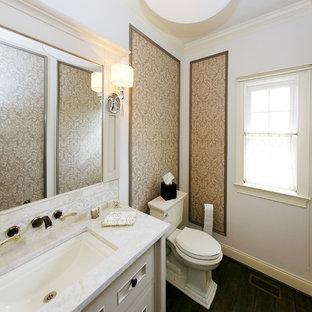 Diseño de aseo tradicional renovado, de tamaño medio, con armarios tipo mueble, puertas de armario blancas, sanitario de dos piezas, paredes beige, suelo de contrachapado, lavabo bajoencimera y encimera de mármol