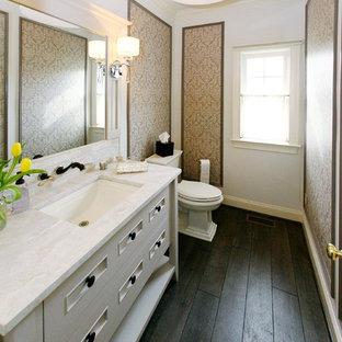 Idées déco pour un WC et toilettes classique de taille moyenne avec un placard en trompe-l'oeil, des portes de placard blanches, un WC séparé, un mur beige, un sol en contreplaqué, un lavabo encastré, un plan de toilette en marbre et un plan de toilette blanc.