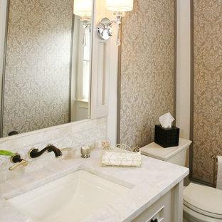 На фото: туалет среднего размера в стиле современная классика с фасадами островного типа, белыми фасадами, раздельным унитазом, бежевыми стенами, полом из фанеры, врезной раковиной, мраморной столешницей и белой столешницей с