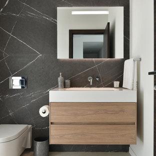 Exemple d'un WC et toilettes tendance avec un placard à porte plane, des portes de placard en bois brun, un WC suspendu, un mur blanc, un sol gris et un plan de toilette blanc.