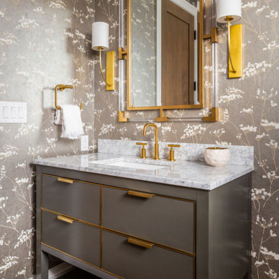 Example of a mid-sized transitional wallpaper, dark wood floor and brown floor powder room design in Denver with flat-panel cabinets, marble countertops, white countertops, gray cabinets, gray walls, an undermount sink and a freestanding vanity