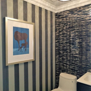 Immagine di un piccolo bagno di servizio minimal con ante lisce, ante nere, WC monopezzo, piastrelle nere, lastra di vetro, pareti nere, pavimento in marmo, lavabo integrato, top in marmo, pavimento nero e top bianco