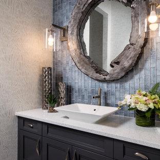Cette photo montre un WC et toilettes bord de mer avec un placard avec porte à panneau encastré, des portes de placard noires, un carrelage bleu, un mur gris, une vasque, un sol gris et un plan de toilette blanc.