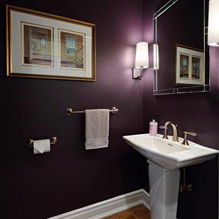 ニューヨークの小さいトラディショナルスタイルのおしゃれなトイレ・洗面所 (一体型トイレ、紫の壁、無垢フローリング、ペデスタルシンク、茶色い床) の写真