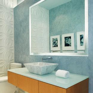 Inredning av ett modernt turkos turkost toalett, med ett fristående handfat och bänkskiva i glas