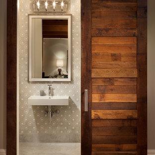 Cette photo montre un WC et toilettes chic de taille moyenne avec un mur multicolore, un lavabo suspendu et béton au sol.