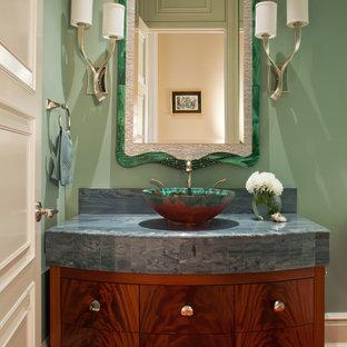 Cette image montre un WC et toilettes traditionnel avec une vasque, un placard à porte plane, des portes de placard en bois sombre et un plan de toilette bleu.
