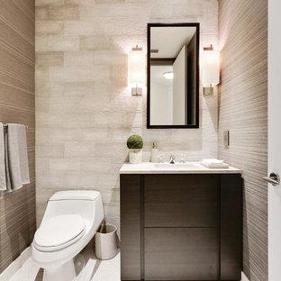 Cette image montre un petit WC et toilettes design avec un placard à porte plane, un WC à poser, un carrelage gris, un carrelage de pierre, un mur gris, un sol en marbre, un lavabo encastré, un plan de toilette en marbre et des portes de placard en bois sombre.