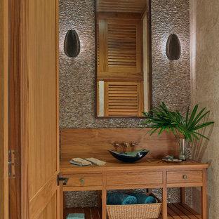 マイアミのトロピカルスタイルのおしゃれなトイレ・洗面所 (家具調キャビネット、木製洗面台、ベッセル式洗面器、中間色木目調キャビネット、ベージュのタイル、ブラウンの洗面カウンター) の写真