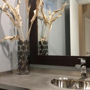 Неиссякаемый источник вдохновения для домашнего уюта: маленький туалет в современном стиле с плоскими фасадами, темными деревянными фасадами, синими стенами, полом из цементной плитки, монолитной раковиной, столешницей из нержавеющей стали и серым полом