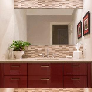 Пример оригинального дизайна: маленький туалет в современном стиле с врезной раковиной, красными фасадами, столешницей из искусственного камня, каменной плиткой, серыми стенами, бежевой плиткой, плоскими фасадами, полом из керамогранита, бежевым полом и серой столешницей