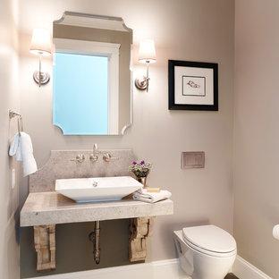 На фото: туалеты в классическом стиле с настольной раковиной, столешницей из известняка, инсталляцией, серой плиткой, серыми стенами и полом из керамогранита