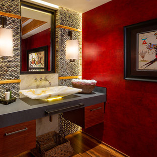他の地域の中くらいのラスティックスタイルのおしゃれなトイレ・洗面所 (フラットパネル扉のキャビネット、石タイル、無垢フローリング、ソープストーンの洗面台、グレーの洗面カウンター、マルチカラーのタイル、赤い壁、ベッセル式洗面器) の写真