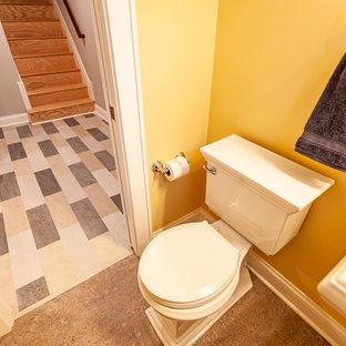 Imagen de aseo clásico renovado con sanitario de una pieza, paredes amarillas, suelo de linóleo, lavabo con pedestal y suelo beige