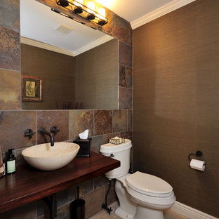 Small traditional cloakroom in New York with a two-piece toilet, multi-coloured tiles, brown walls, travertine flooring, a vessel sink, wooden worktops and slate tiles.