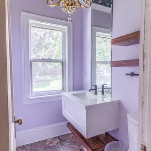 Foto de aseo clásico renovado, de tamaño medio, con armarios con paneles empotrados, puertas de armario blancas, sanitario de una pieza, paredes púrpuras, suelo de baldosas de cerámica, lavabo integrado, encimera de mármol, suelo beige y encimeras blancas