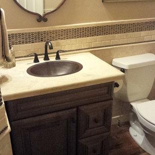 На фото: маленький туалет в современном стиле с накладной раковиной, фасадами с выступающей филенкой, темными деревянными фасадами, раздельным унитазом, бежевой плиткой, каменной плиткой, бежевыми стенами и паркетным полом среднего тона с