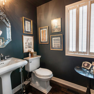 Inspiration for a timeless dark wood floor powder room remodel in Toronto with a pedestal sink, a two-piece toilet and black walls