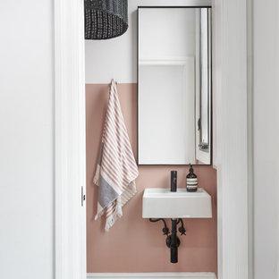 トロントのトランジショナルスタイルのおしゃれなトイレ・洗面所 (ピンクの壁、壁付け型シンク、黒い床) の写真
