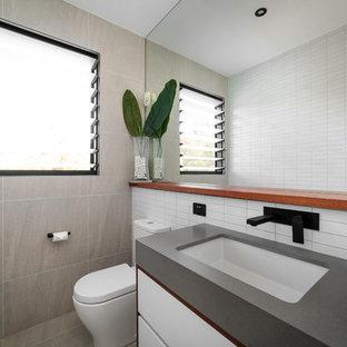 Свежая идея для дизайна: туалет среднего размера в стиле модернизм с плоскими фасадами, серыми фасадами, раздельным унитазом, керамической плиткой, белыми стенами, светлым паркетным полом, накладной раковиной, столешницей из бетона, серым полом и серой столешницей - отличное фото интерьера