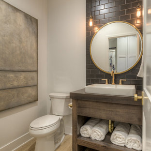Design ideas for a country cloakroom in Omaha with freestanding cabinets, dark wood cabinets, a two-piece toilet, black tiles, white walls, light hardwood flooring, a vessel sink, wooden worktops and beige floors.
