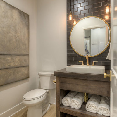 Inspiration for a farmhouse black tile light wood floor and beige floor powder room remodel in Omaha with furniture-like cabinets, dark wood cabinets, a two-piece toilet, white walls, a vessel sink, wood countertops and brown countertops