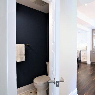 Aménagement d'un petit WC et toilettes classique avec un placard à porte shaker, des portes de placard blanches, un WC séparé, un mur bleu, un sol en carrelage de terre cuite, un lavabo intégré, un plan de toilette en surface solide, un sol multicolore et un plan de toilette blanc.
