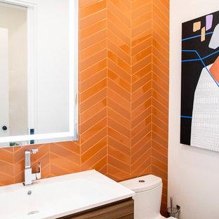 Неиссякаемый источник вдохновения для домашнего уюта: туалет среднего размера в стиле модернизм с плоскими фасадами, фасадами цвета дерева среднего тона, унитазом-моноблоком, оранжевой плиткой, керамической плиткой, белыми стенами, монолитной раковиной, столешницей из искусственного камня и белой столешницей