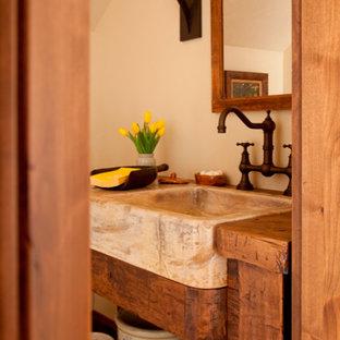 Immagine di un bagno di servizio rustico di medie dimensioni con pareti beige, lavabo da incasso e top in pietra calcarea