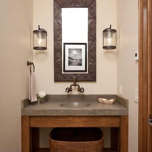 他の地域の中サイズのラスティックスタイルのおしゃれなトイレ・洗面所 (一体型シンク、コンクリートの洗面台、ベージュの壁、グレーの洗面カウンター) の写真