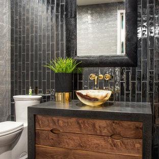 На фото: туалет в стиле лофт с темными деревянными фасадами, унитазом-моноблоком, черной плиткой, черными стенами, настольной раковиной, черным полом и черной столешницей с