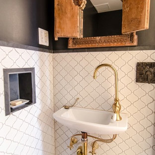 Example of a tuscan black tile powder room design in New York with a wall-mount sink