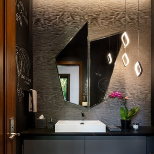 На фото: туалет в морском стиле с плоскими фасадами, серыми фасадами, серой плиткой, черными стенами, полом из галечной плитки, настольной раковиной, серым полом и черной столешницей с