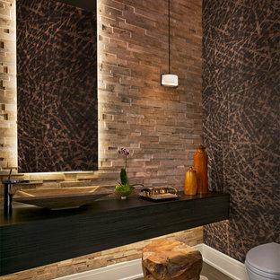 Inspiration pour un WC et toilettes design de taille moyenne avec un WC suspendu, un carrelage de pierre, une vasque, un placard à porte plane, des portes de placard marrons, un carrelage beige, un mur beige, un sol en bois brun et un sol marron.