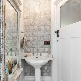 Inspiration for a traditional powder room in Melbourne with a pedestal sink, a two-piece toilet, beige tile, porcelain tile, white walls and medium hardwood floors.