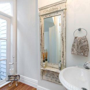 Shabby chic-inspirerad inredning av ett toalett, med ett piedestal handfat, en toalettstol med separat cisternkåpa, porslinskakel, vita väggar, mellanmörkt trägolv och grå kakel