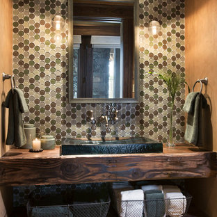 Example of a mountain style powder room design in Other with a vessel sink, wood countertops and brown countertops