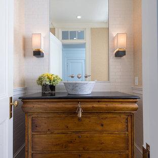 Aménagement d'un WC et toilettes classique avec un placard en trompe-l'oeil, une vasque, des portes de placard en bois brun, un carrelage blanc, un mur beige et un plan de toilette noir.